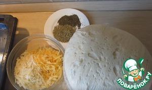 Сыр натираем на крупной терке. Тесто делим на 2 части и руками распределяем по форме смазанной маслом.