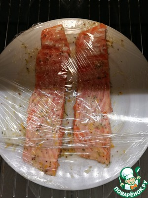 Salmon cut into portions, grease a plate or dish (any ceramic or porcelain) made with oil, spread on her pieces of salmon and lubricates every bite orange oil with a brush. On top sprinkle with fine sea salt. Cover with a plate (not foil!), and cling film. Normal film can withstand a minimum temperature of 100 gr. if it is of good quality. Salmon leave for 15 minutes, preheat the oven to 85-90 degrees and then put the salmon in the oven in a dish on a wire rack for 20 to 25 minutes.