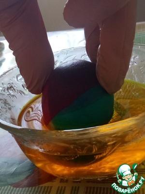 Берем наше яйцо и уже оставшуюся не закрашенную часть опускаем уже в другой краситель.