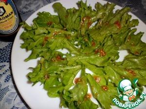 На тарелку первым слоем выкладываем листья салата, нарвав их на кусочки. Поливаем соусом.