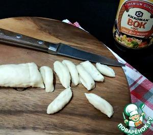 Пока варится суп, подготовим чесночные галушки.   В емкости соединить воду, растительное масло, соль и измельченный чеснок (я натерла на мелкой терке). Тщательно перемешать и начать вводить муку. У меня ушло 60 г муки. Тесто должно получиться мягкое, слегка прилипает к рукам. Раскатать тесто в жгут (длиной ~25см) и нарезать маленькими кусочками.
