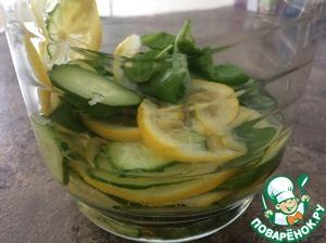 В кувшин положить лимон, немного помять толкушкой. Добавить базилик и огурец, немного помять. Залить сиропом.