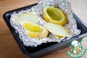 Тем временем срезать верхушку у готового картофеля и аккуратно с помощью ложки достать середину. Этот картофель можно использовать в супе или сделать пюре.