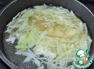 Выложить в бульон порезанный картофель и нашинкованную капусту.   Варить 10 минут.