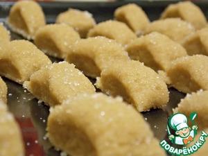 Разделить на несколько частей и раскатать в длину (колбаски ). Обвалять хорошенько в сахаре. Затем порезать колбаски на кусочки. Положить на противень.