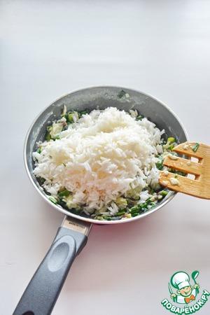 Рис достаньте из воды, вскройте пакетики, всыпьте готовый рис к черемше и перемешайте
