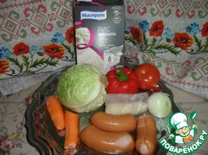 While boiling water for cooking rice, prepare the products. Sausage cut by slices, onion - half rings, carrot grate on a coarse grater, bell peppers and tomatoes - small cubes. Cabbage chop thin strips, green would Nachinaem.