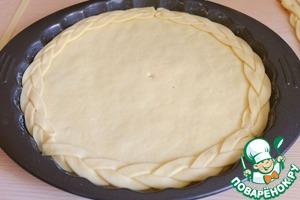 Край пирога смазать водой, перенести косички на поверхность пирога