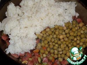 Добавляем в сковороду отваренный рис и консервированный зеленый горошек. Солим.