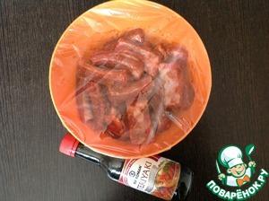 В миску добавить ребрышки, соевый соус, томатный соус, натёртый имбирь, измельчённый перец чили, чесночный порошок, кунжутное масло, сладкую паприку. Хорошо перемешать. Убрать на 1-2 часа в прохладное место. Солить лучше в конце маринования, за 20-30 минут до запекания.