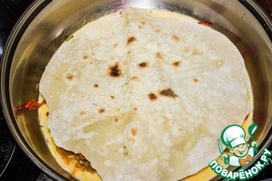 Put on top of the cake, chapatti, lightly press and keep on fire for about a minute. Add to the pan the remaining oil, flip the tortilla to other side and fry for another 1-2 minutes.