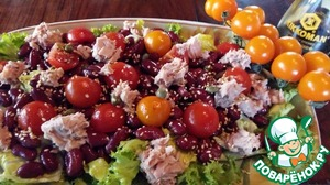 On a dish place a layer of salad leaves, drizzle with dressing. On top place the beans, tomatoes and tuna fish pieces, pour with the dressing, sprinkle with capers and lightly toasted sesame seeds.