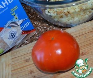 Погрузить в кипяток пакетик с рисом, варить 25 минут.   В это время помидор вымыть, нарезать средним кубиком.   Выложить к сыру.