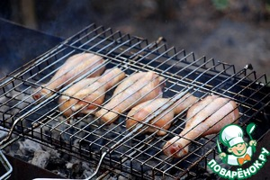 Legs spread on the grill and fry on the coals on both sides until cooked.