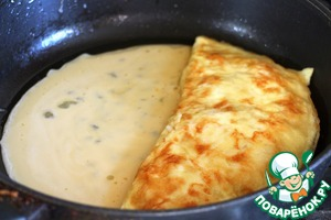 Pour in the vacated space remains omletes mixture, wait until the edges will grab and flip her omelette with filling.