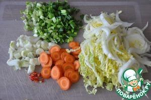 Пока варится рис, моем и чистим овощи.   Лук режем кубиками, морковь кружками, пекинскую капусту полосками. Также сразу мелко режем зелёный лук и перец чили.   Пекинской капусты берём белую часть, она сочнее.