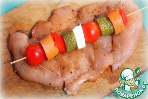 On pre-soaked wooden skewers thread pieces of sausage, pickles, peppers, smoked cheese and cherry tomatoes (the stuffing can be any, according to your taste). Put the filling on the middle of the breast.