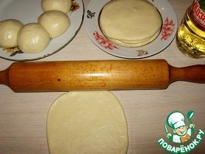 Раскатать скалкой из шарика теста небольшую лепёшку. Смазать обе стороны маслом