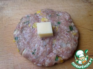 Now take a piece of meat the size as a regular hamburger. Make round flat cakes with a thickness of at least 1 cm, and in the center of the tortilla put the cheese cube.