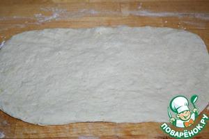 Подошедшее тесто выложить на рабочую поверхность, присыпанную мукой, обмять и разделить на две равные части. Каждую раскатать в пласт толщиной примерно 1 см.