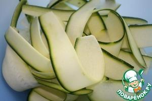 Кабачки нарезать тонкими лентами овощерезкой и выложить в глубокую миску.