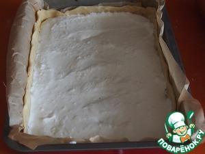 Тесто раскатать в тонкий пласт, уложить его в смазанную маслом или выложенную бумагой для выпечки форму. Сформировать бортики. На тесто распределить начинку, сверху разложить пластинки чеснока.