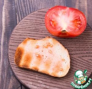 Натереть хлеб чесноком, еще раз хорошо смазать маслом с соевым соусом, прямо слегка пропитать.   Разрезать помидор на половинки и хорошо натереть помидором хлеб.