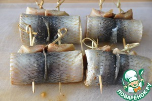 Wrap herring in a roll held together by a skewer.