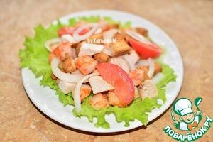 На тарелку выложить листы салата, сверху салат горкой, дополнить дольками помидора;