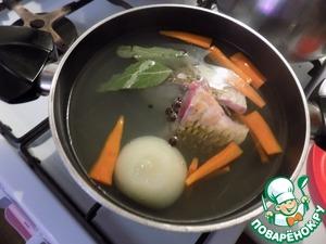 Выкладываем морковь, крупно порезанную брусочками и целую луковицу. Солим по вкусу. Варим до готовности. Выкладываем рыбу, перцы и лавровые листы. Рыба варится быстро.