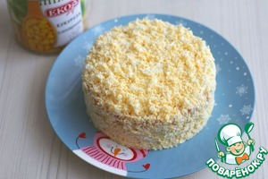Кольцо убрать. Натереть на на мелкой терке два яйца, боковую часть салата припорошить натертой яичной соломкой, дополнительно присыпать верх салата.