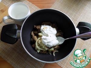 Лук отправляем к печени в кастрюлю, добавляем сметану и горячую воду.