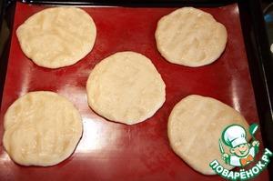 Разделите тесто на 7 равных кусочков, подкатайте в тугие шарики, закройте пленкой и оставьте на 10 минут. Раскатайте в аккуратные лепешки толщиной примерно 5 мм. Можно раскатать тесто в пласт и нарезать квадратами со стороной 5-7 см. Разложите заготовки на застеленные бумагой противни, закройте пленкой и оставьте на 45-60 минут при комнатной температуре.