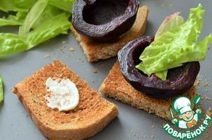Хлеб нарезать на небольшие кусочки, у свеколок чуть срезать донце.   На кусочек хлебушка выложить чуть сырной смеси.    Поставить на неё свеклу, с одной стороны выложить зелень салата (имитируем ботву редиса).