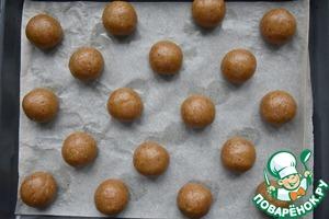 Разделить тесто на кусочки, примерно 55 граммов каждый. Скатать шарики и выложить их на противень, застеленный пергаментной бумагой. Выпекать печенье в духовке, разогретой до 200 градусов не более 15 минут.