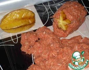 У карамбол отрезать небольшой кусочек плода со стороны плодоножки. На столе расстелить пищевую пленку. Уложить фарш в полости карамболей, соединить их обрезанными кончиками и затем полностью покрыть фаршем.