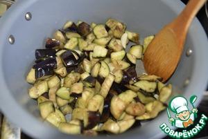 Как только появляется аромат чеснока, кладём в кастрюлю баклажаны и обжариваем, постоянно помешивая 5 минут. Убираем баклажаны на тарелку.