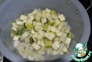 Лук и цуккини моем, чистим и режем такими же кубиками, как и баклажаны. Добавляем в кастрюлю масло, обжариваем пару минут лук, далее добавляем цуккини и обжариваем всё на среднем огне 5 минут.