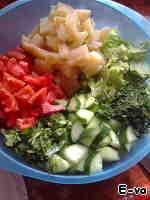 Огурцы разрезаем на 4 части и шинкуем не очень тонко. На помидорах делаем крестообразные насечки на кожице, заливаем на пару минут кипятком и удаляем пленку. Зелень мелко рубим. Картофель нарезаем брусочком. Листья салата можно нарвать руками, а можно нарезать, не слишком тонко.