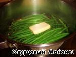 После этого добавляем к фасоли кусочек сливочного масла и продолжаем готовить под крышкой ещё около 5 минут. За это время фасоль пропарится, но останется немного хрустящей, что и является идеальной степенью её готовности для данного блюда.