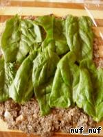 На разделочной доске расстелить пищевую плёнку и выложить на неё слой остывшей грибной смеси. Поверх смеси выложить листочки шпината.