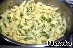 Ракушки с горохом возвратить в кастрюлю. Добавить оставленные 1/2 стакана жидкости, аспарагус, чесночный порошок, оливковое масло, зеленый лук, базилик, мяту, цедру лимона, соль и перец по-вкусу. Все хорошо перемешать, накрыть крышкой и ставить минут на 5.