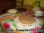 Заранее для украшения торта откладываем по 1 стакану каждого крема, убираем пока в холодильник. Ну вот, самое сложное позади. Приступаем к сборке торта.    1) Каждый корж разрезаем вдоль, получится 4 (2 белых, 2 черных). Пропитываем каждый корж апельсиновой пропиткой.    2) Берём шоколадные корж и смазываем белым кремом, потом берём белый корж и смазываем его коричневым кремом.