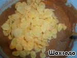 Тесто делим на 2 части: в одну добавляем 3 чайных ложки какао и хлопья (немного хлопьев оставляем для присыпки верха пирога), вторую часть теста не трогаем.