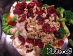 3аправить salad and add the sunflower seeds and dried cranberries (raisins).