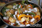 The vegetables in the pan, season with sweet paprika powder, salt, oregano and mix gently. Add strips of tomatoes and crumbled feta cheese or feta.