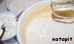 На малой скорости миксера небольшими порциями ввести йогурт, чередуя его с мукой.