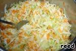 В сотейник налить подсолнечное масло, добавить лук и морковь, слегка обжарить и затем добавить нашинкованную капусту. Все перемешать и тушить под крышкой минут 5-10.