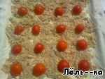 All spread on the dough evenly on top decorate with halved cherry tomatoes.