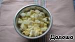 Яблоки очистить от кожуры и нарезать кубиками, выложить в ёмкость и сбрызнуть соком 1/2 части лимона.